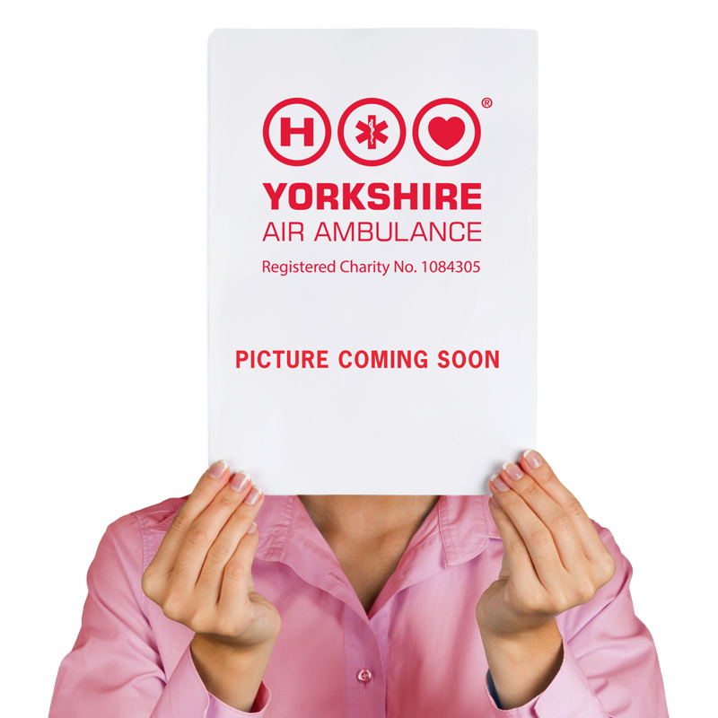 Lady holding board over her face with Yorkshire Air Ambulance saying Picture Coming Soon