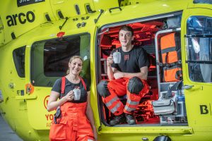 Image of paramedics sat in helicopter with hot chocoalte