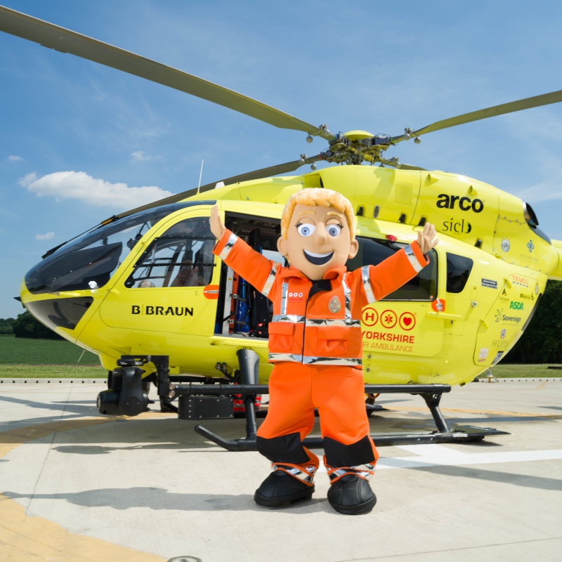 Image of Yorkshire Air Ambulance mascot Polly Paramedic in from of helicopter