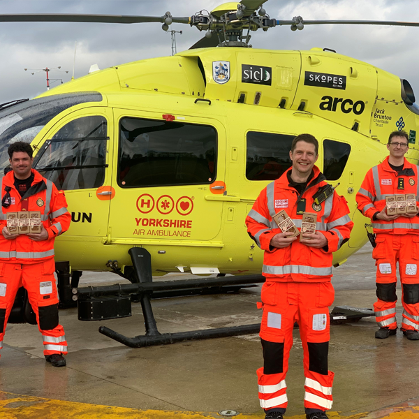 Image of YAA crew in front of YAA helicopter holding boxes of Lottie Shaw's YAA Ginger Parkin Biscuits