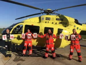 Photo of Yorkshire Air Ambulance crew in front of helicopter holding up letters that spell out Thank You