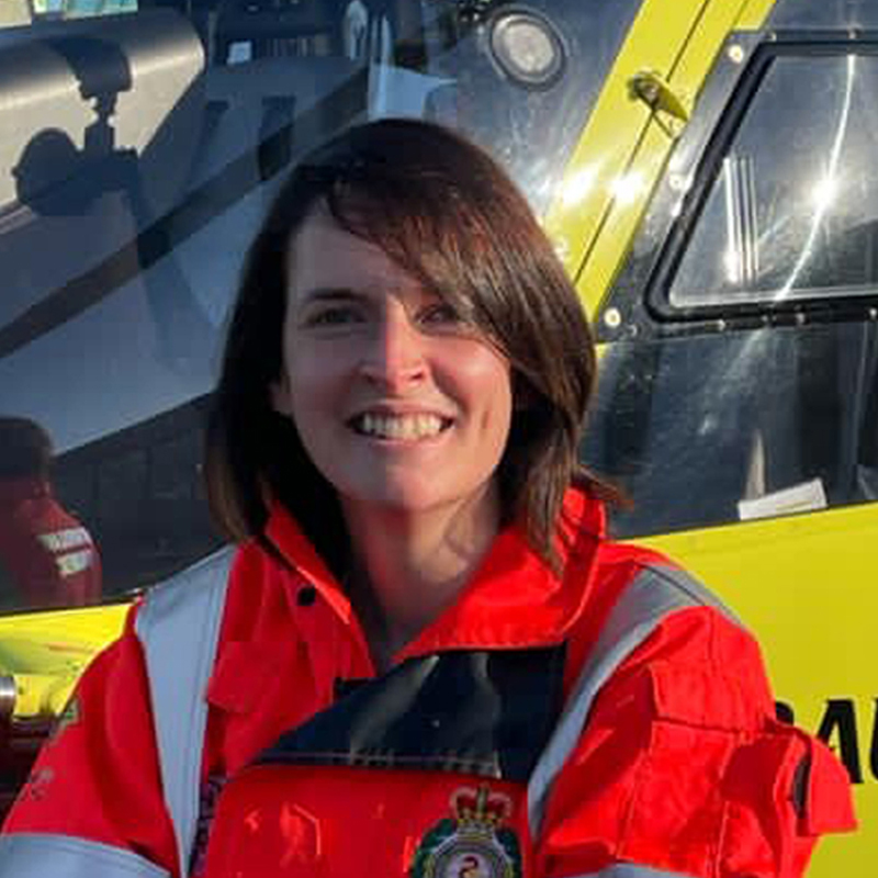 Photo of HEMS Paramedic Gemma Richmond in front of Yorkshire Air Ambulance helicopter