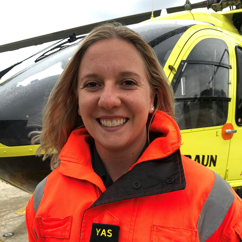 Photo of HEMS Paramedic Georgina Godfrey in front of Yorkshire Air Ambulance helicopter