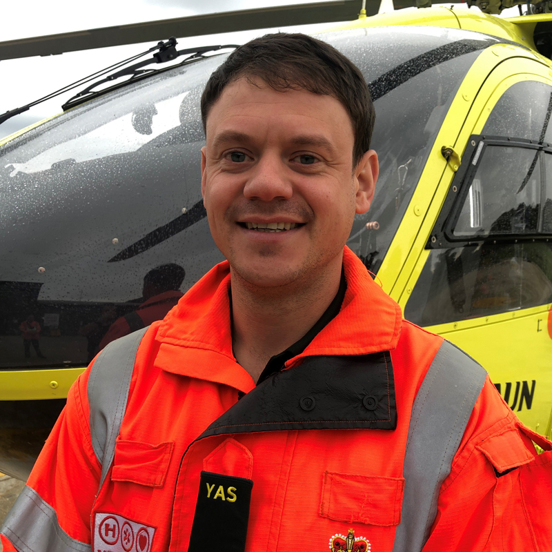 Photo of HEMS Paramedic Michael Williams in front of Yorkshire Air Ambulance helicopter