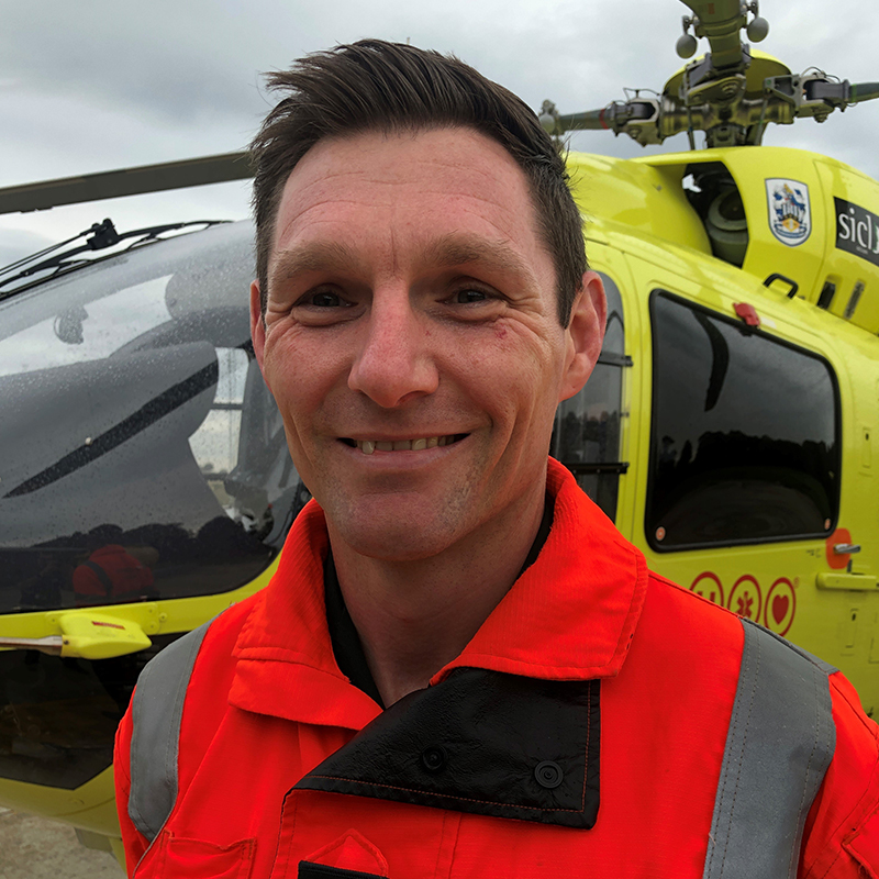 Photo of HEMS Paramedic Steven Dawber in front of Yorkshire Air Ambulance helicopter