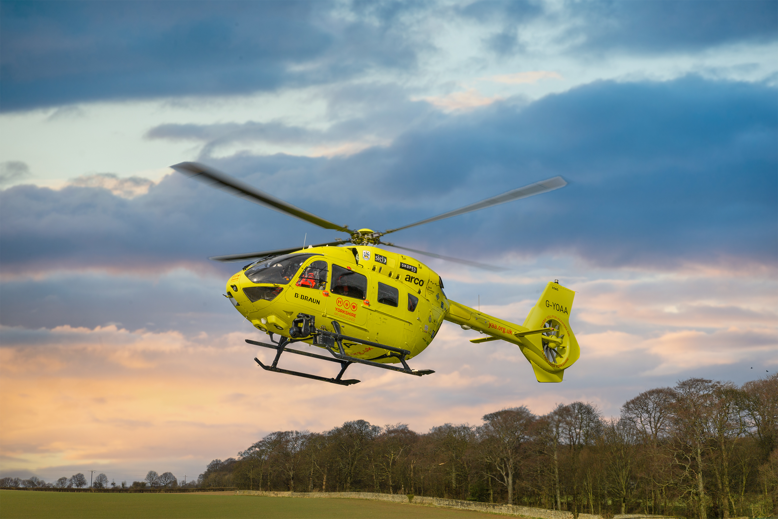 Image of Yorkshire Air Ambulance helicopter flying in blue and pink sky