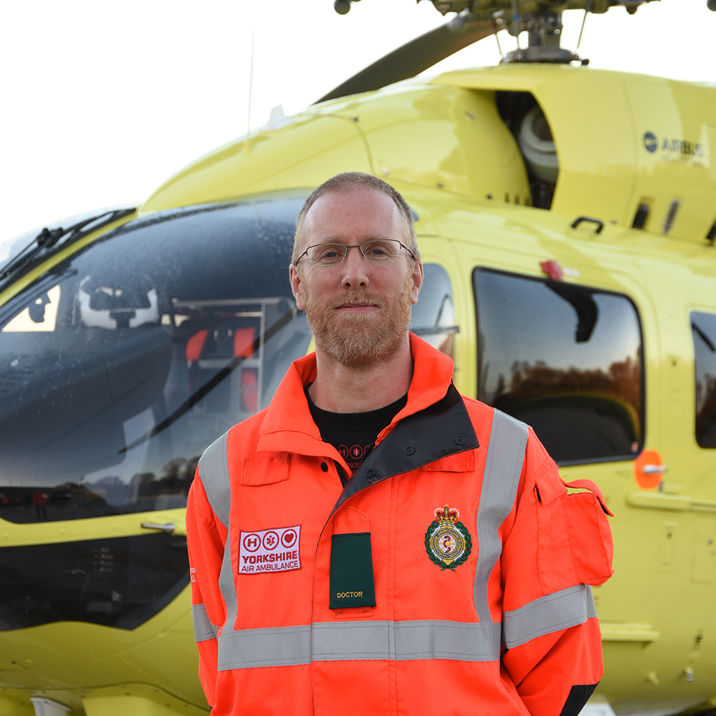 Yorkshire Air Ambulance Doctor Neil Sambridge stood in front of a yellow YAA helicopter