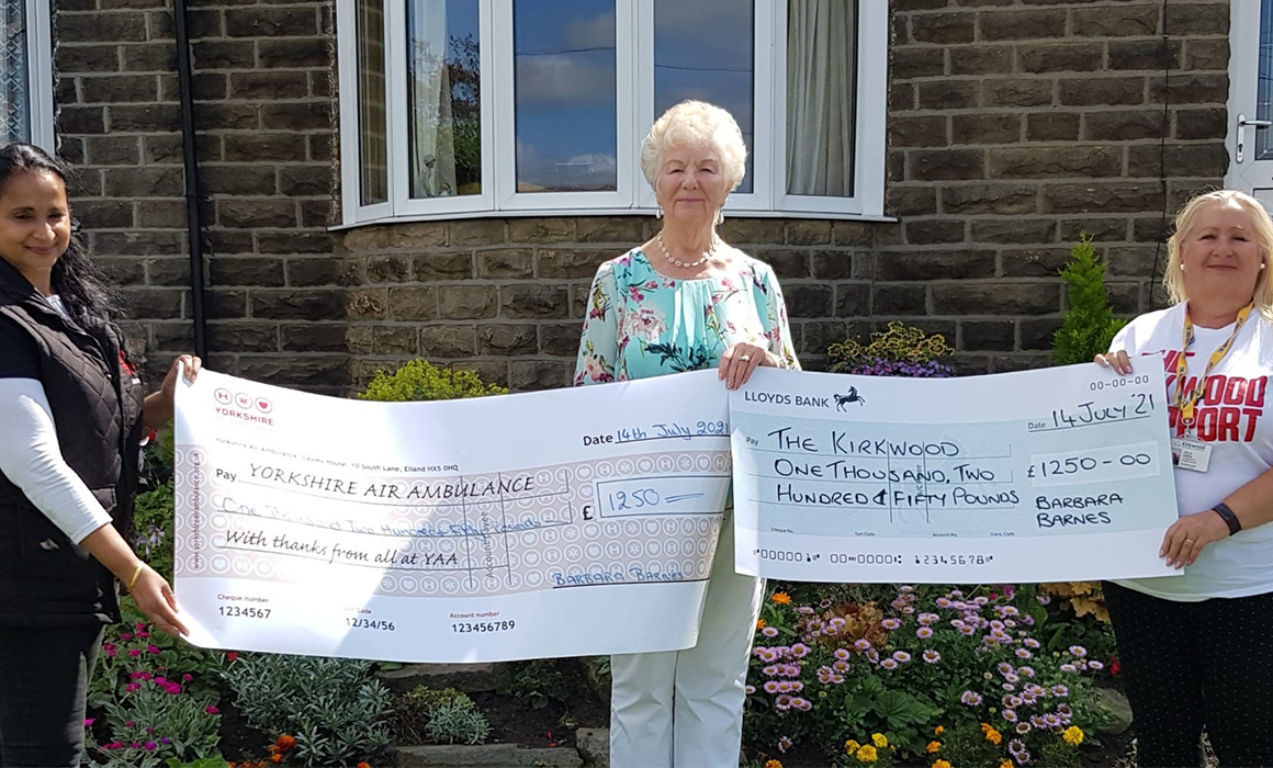 Photo of Barbara Barnes presenting two giant cheques to Angela Vyas from Yorkshire Air Ambulance, in front of a house and flowers