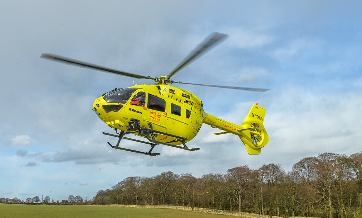 Yorkshire Air Ambulance helicopter G-YOAA lifting off with trees in background